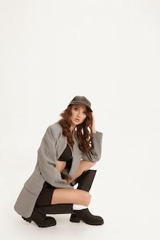 Menina peituda modelo com maquiagem perfeita em uma jaqueta da moda e botas posando no fundo branco isolado estúdio de moda tiro