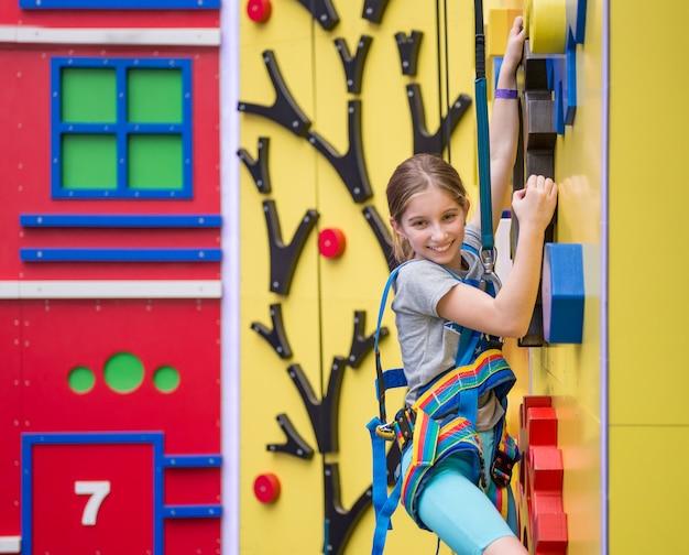 Menina pendurada na parede de escalada