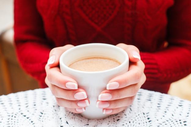 Menina pendurado café quente na xícara