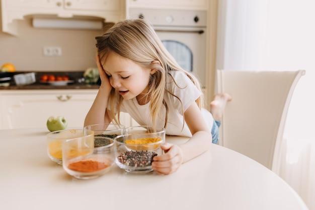 Menina pensando no que cozinhar na cozinha
