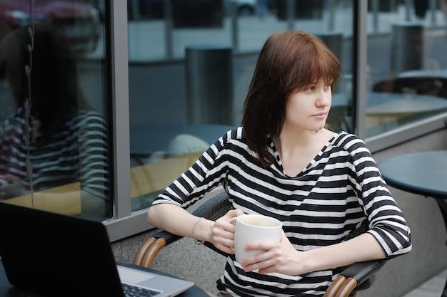 Menina pensativa, bebendo café e usando o laptop em um café ao ar livre
