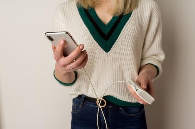 Menina pensativa brinca no telefone e o infecta pelo banco de energia. banco de poder nas mãos da garota. usando banco de energia e jogando.