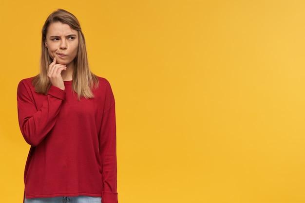 Menina pensativa com cabelo loiro. vestindo um suéter vermelho. os lábios franziram como se duvidasse de alguma ideia. espaço de cópia grátis para seu texto