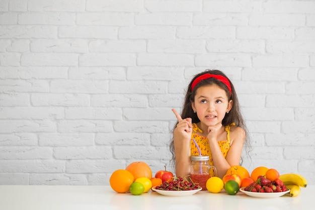 Menina pensativa com frutas frescas coloridas apontando para cima