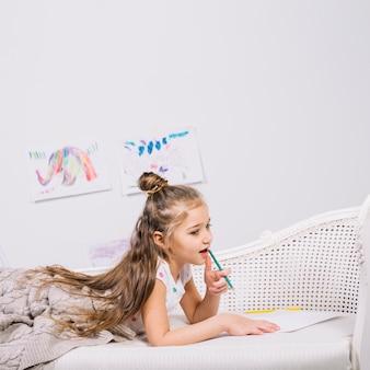Menina pensativa com lápis e papel no sofá