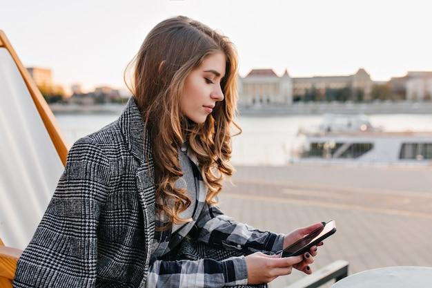 Menina pensativa com mensagem de texto de penteado encaracolado, sentada na poltrona numa manhã fria