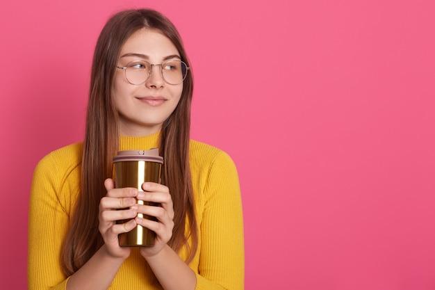 Menina pensativa com thermomug nas mãos, senhora parece pensativa, olhando pensativa e sorrindo de lado, desfrutando de bebida quente