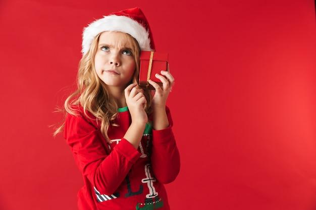 Menina pensativa com uma fantasia de natal isolada, segurando caixas de presente