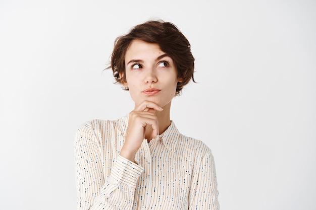 Menina pensativa de blusa tocando o queixo, olhando para o canto superior direito e pensando, fazendo uma escolha, de pé sobre uma parede branca