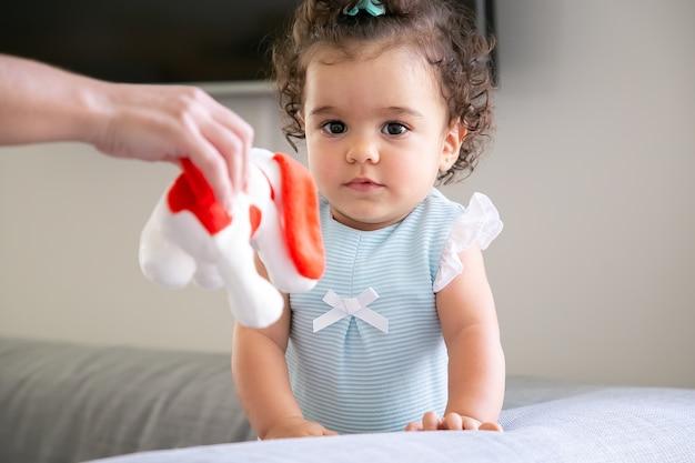 Menina pensativa de cabelo encaracolado escuro enquanto a mãe dela dando um brinquedo vermelho e branco para a criança. criança em casa e conceito de infância