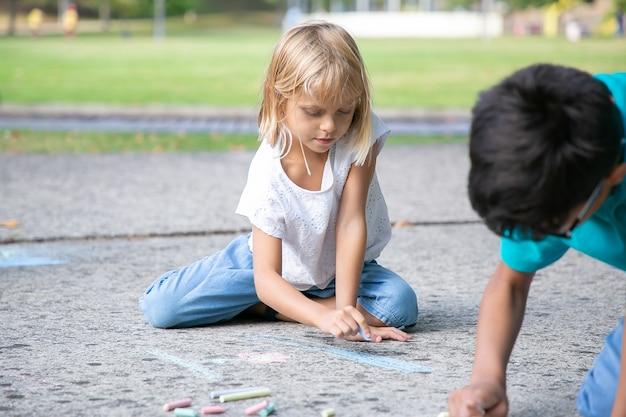 Menina pensativa de cabelos muito louros sentado e desenhando com pedaços coloridos de giz. vista frontal. conceito de infância e criatividade