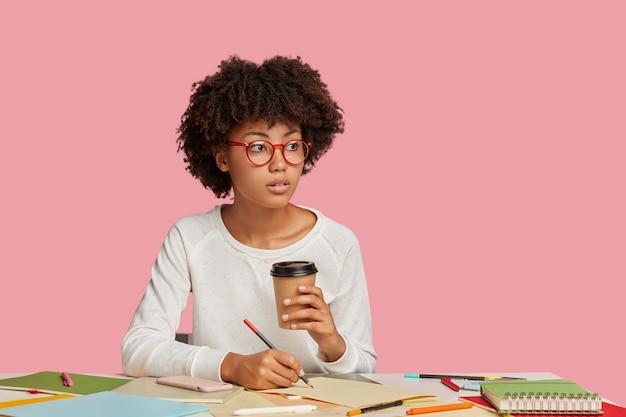 Menina pensativa, de pele escura, com óculos redondos, faz anotações em uma folha de papel em branco, segura café para viagem