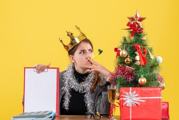 Menina pensativa de vista frontal com coroa sentada à mesa segurando o documento árvore de natal e coquetel de presentes
