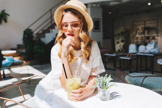Menina pensativa e cacheada com chapéu de palha vintage e vestido branco esperando namorado no café