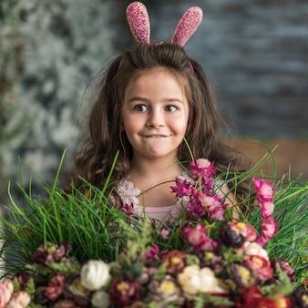 Menina pensativa em orelhas de coelho com flores
