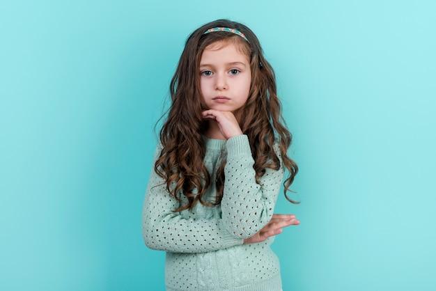 Menina pensativa em pé no fundo azul