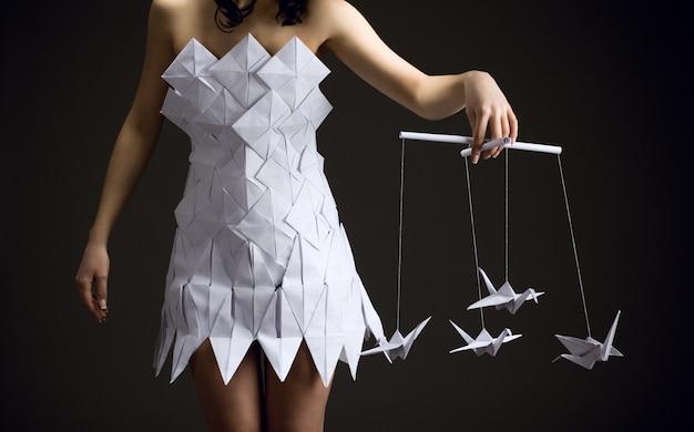 Menina pensativa em um vestido de origami tem um pássaro de origami nas mãos.