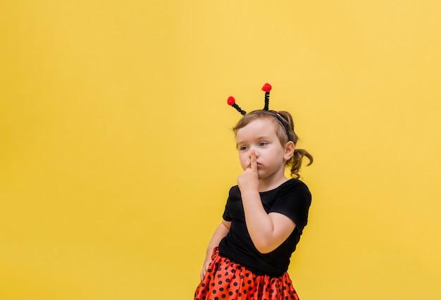Menina pensativa em uma fantasia de joaninha aponta o dedo