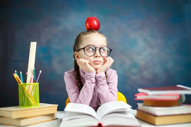 Menina pensativa escola primária com maçã na cabeça, tendo uma ideia
