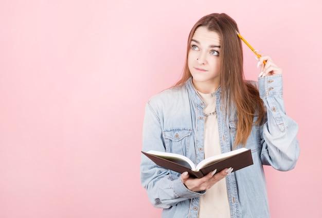 Menina pensativa, escritora de cabelos escuros, segura um livro nas mãos, olha para o canto, coça a cabeça com um lápis e pensa. dia internacional dos escritores