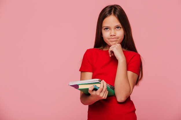 Menina pensativa no vestido vermelho, segurando o livro e olhando