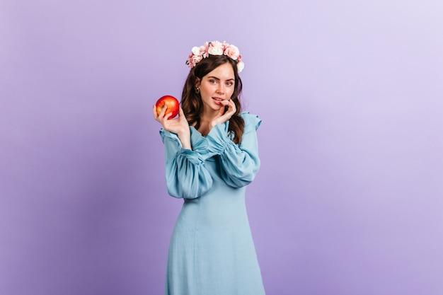 Menina pensativa olhando astutamente, segurando uma maçã apetitosa. retrato do modelo com coroa de flores na parede lilás.