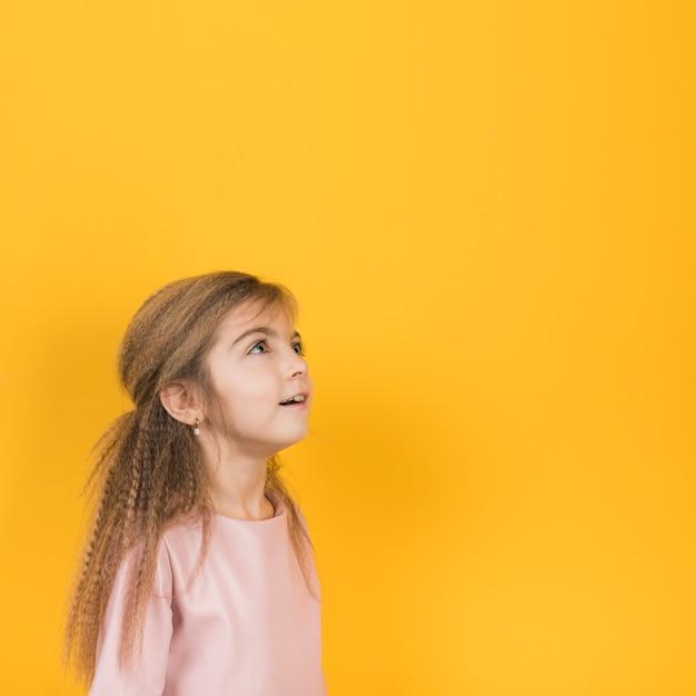 Menina pensativa olhando no fundo amarelo