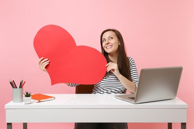 Menina pensativa olhando para cima sonhando segurar coração vazio vermelho em branco sentar trabalhar na mesa branca com laptop pc