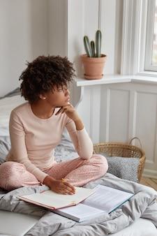 Menina pensativa posando em casa em uma cama confortável