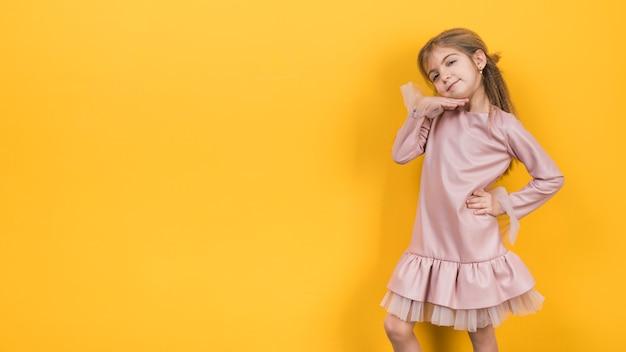 Menina pensativa posando em fundo amarelo