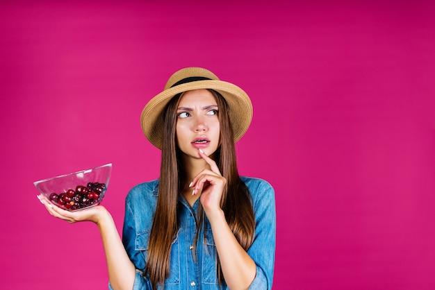 Menina pensativa segura o prato com cerejas e olha para o lado direito
