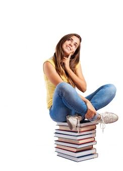 Menina pensativa sentada em livros