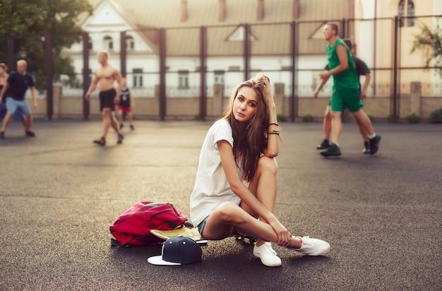 Menina pensativa sentada no skate