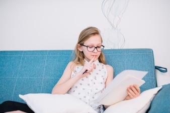 Menina pensativa sentada no sofá com lápis e papel