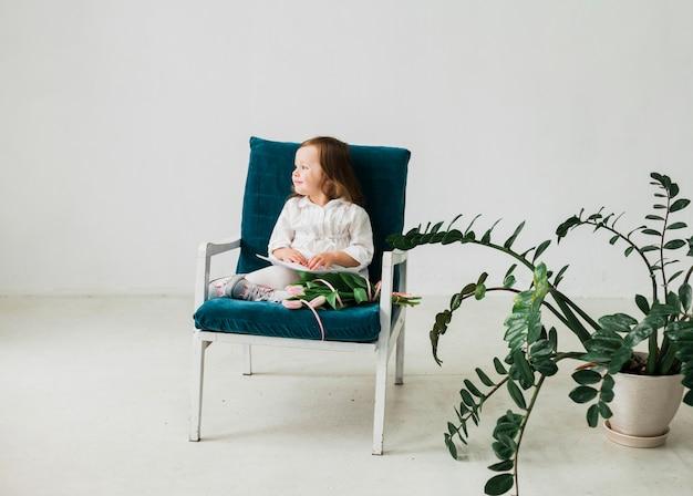 Menina pensativa sentado na poltrona