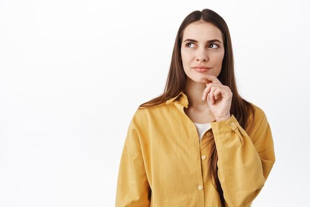 Menina pensativa tomando decisões, tocando o queixo e olhando para o lado, pensativa, ponderando sobre a escolha, encostada na parede branca e inventando uma ideia, procurando uma solução