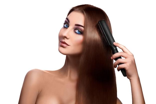 Menina penteando o cabelo comprido perfeito e olhando para a frente com olhos azuis em branco