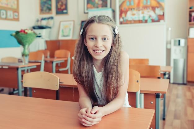Menina pequena adorável da escola com as notas e os lápis ao ar livre.