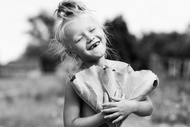 Menina pequena aldeia posando sob uma bardana