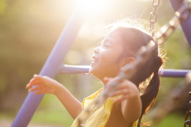 Menina pequena asiática feliz que voa no balanço no campo de jogos no tempo do por do sol em movimento borrado