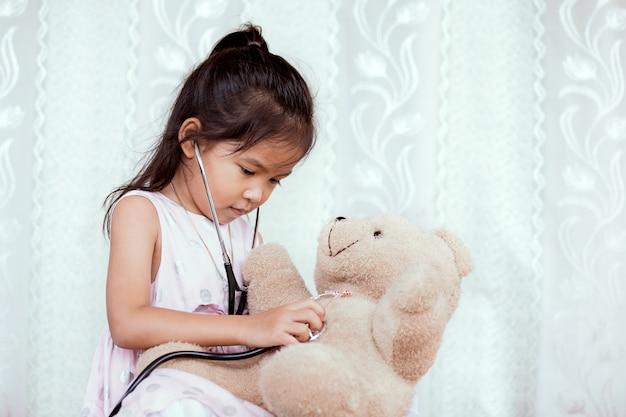 Menina pequena asiática pequena com estetoscópio que joga o doutor com urso de peluche no tom de cor do vintage