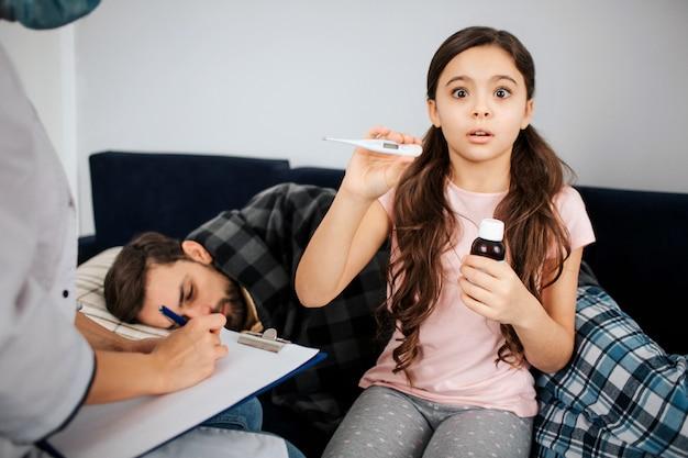 Menina pequena assustada segurando o termômetro e a garrafa de xarope nas mãos. médica, sente-se ao lado dela e escreva. jovem doente, deitado na cama e dormindo.