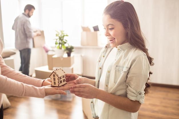 Menina pequena bonita e alegre está segurando uma casa de madeira nas mãos dela. ela está compartilhando com a mãe. o pai está segurando uma caixa com coisas que precisam ser desembaladas.