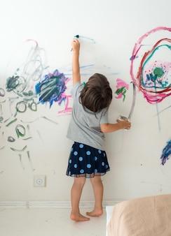 Menina pequena bonito encaracolado da pintura da criança com pinturas cor e parede da escova.