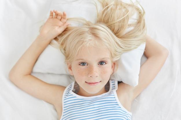 Menina pequena bonito que descansa na cama branca, olhando com olhos azuis. sonhadora menina loira de olhos azuis no quarto confortável