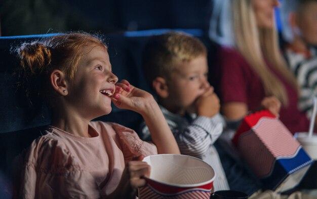 Menina pequena com família sentada e assistindo filme no cinema, comendo pipoca.