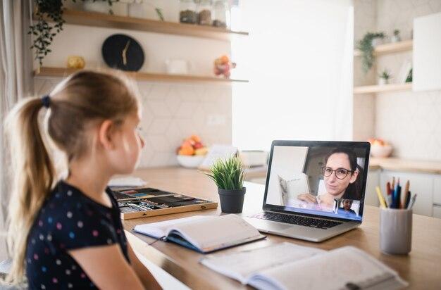 Menina pequena com laptop aprendendo pela internet dentro de casa em casa