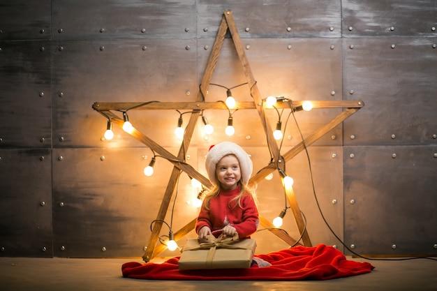 Menina pequena com presentes no natal sentado no cobertor vermelho pela estrela