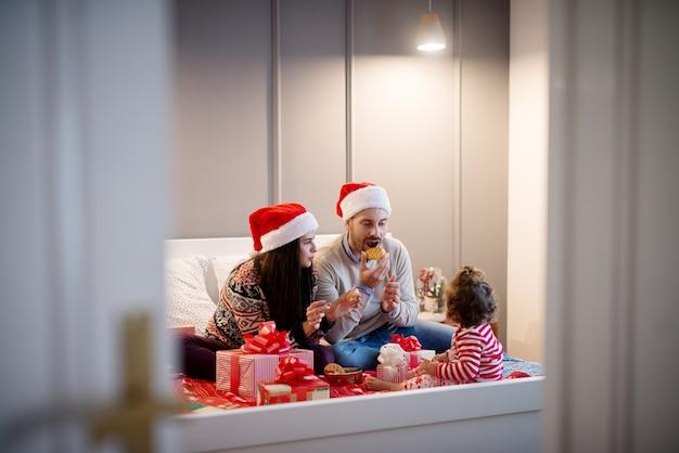 Menina pequena criança encaracolado olhando nos pais enquanto come e brinca com biscoitos na cama para as férias de natal.