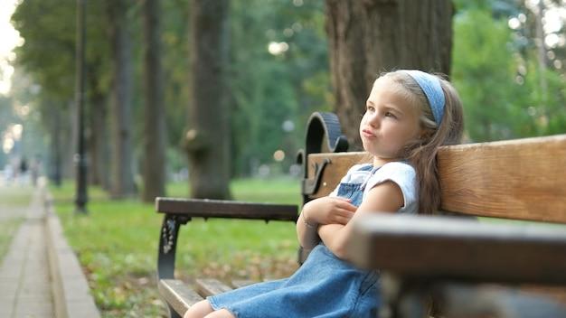 Menina pequena criança irritada sentada sozinha num banco no parque de verão.